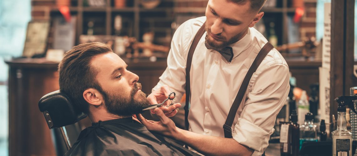 Side view of young bearded man getting beard haircut by hairdresser while sitting in chair at barbershop